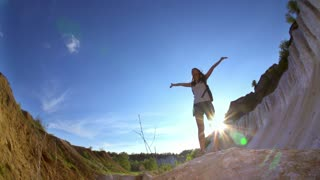Tourist woman is hiking in mountains. Athletic woman-hiker is happy to reach the top and spinning around her to enjoy the view and the sun in the mountains. Slow motion filmed at 240 fps. Fish eye.