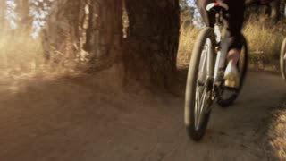 Tracking close up shot of a man and a woman riding bicycles in a forest