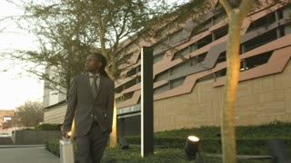 Steadicam shot of African American business man walking with silver brief case in the city.