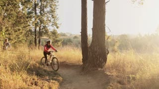 Steadicam shot of mountain biking couple riding on bike trail at sunset.