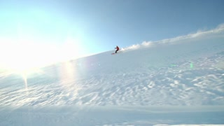 Tracking shot of a skier riding down the slope in sunlight