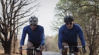 Steadicam shot of two healthy men cycling on road bicycle with speed down the road.