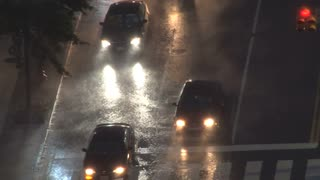 Traffic Fights Through Pounding Rain at Intersection