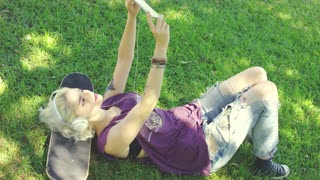 Trendy hipster young woman taking a selfie as she relaxes in a park in the shade of the tree with her skateboard listening to music