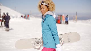Trendy young woman carrying her snowboard
