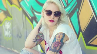 Trendy young woman with a pierced lip and vampire tattoo wearing stylish sunglasses sitting on a sidewalk leaning against a graffiti covered wall