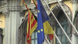Trio of Flags Waving Outside Building in Spain 2