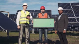 Trio of solar panel engineers with green screen panel and executive surrounded by large collector arrays outside