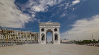 triumphal arch timelapse hyperlapse  with national man and woman statues and the central part of the city with clouds in summer day in Astana, Kazakhstan. 4K