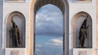 triumphal arch timelapse with solders statues and the central part of the city with clouds in summer day in Astana, Kazakhstan. 4K