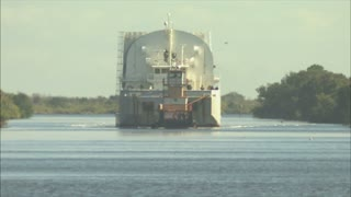 Tugboat Pulling Barge Down Waterway