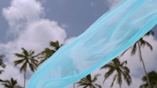Turquoise sarong fluttering on wind against the palm trees