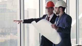 Two architects discussing building plan standing near window