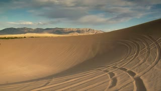 Two Atv Riders Circle Large Sand Dune