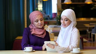 Two Beautiful Muslim Girl Using Tablet In Cafe