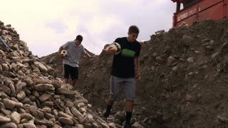 Two Boys Carrying Soccer Balls in Quarry