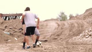 Two Boys Playing Soccer on Dirt 2