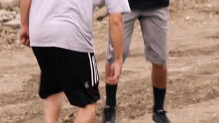 Two Boys Playing Soccer on Dirt