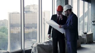 Two businessmen discussing building plan on paper while looking through the window