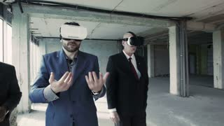 Two businessmen in oculus rift goggles talking and watching plan of future building and using 360 degree interface