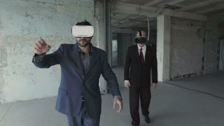 Two businessmen in oculus rift goggles talking and watching plan of future building
