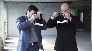 Two businessmen in suits wearing on oculus rift and discussing something while gesturing