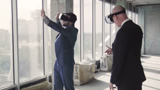 Two businessmen in unfurnished room talking near window and gesturing in oculus rift