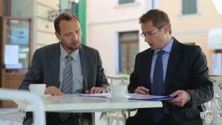 Two businessmen signing contract in the restaurant