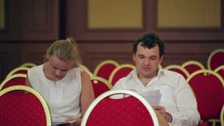 Two businesspeople making notes in the conference hall