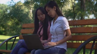 Two businesswoman or students sitting on the bench using laptop in the park. Happy asian women at the meeting have business conversation. Attractive professional woman talking and show on the computer