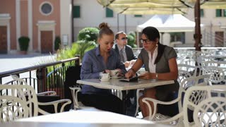 Two businesswoman sitting in cafe and talking together, outdoors