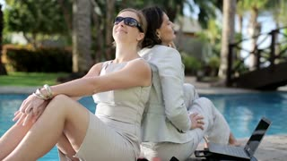 Two businesswomen after work relaxing by the poolside