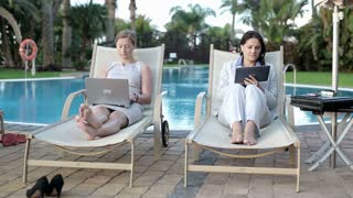 Two businesswomen lying on sunbed and working using technology