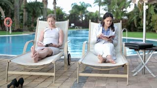 Two businesswomen reading books on sunbed by the poolside