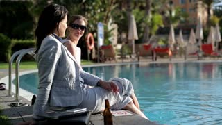 Two businesswomen relaxing by the poolside