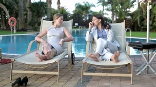 Two businesswomen relaxing on sunbed by poolside