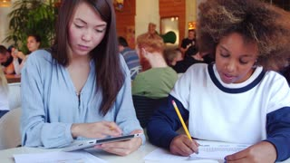 Two cheerful girls - asian and black, chatting and working together in cafe