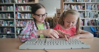 Two cheerful little schoolgirls typing on computer keyboard in school library
