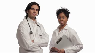 Two confident doctors looking at camera, white background