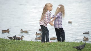 Two cute little girls at park feeding ducks