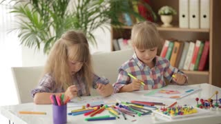 Two cute little girls sitting at desk drawing and smiling at camera
