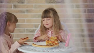 Two cute little girls sitting at table at cafe eating pizza and smiling