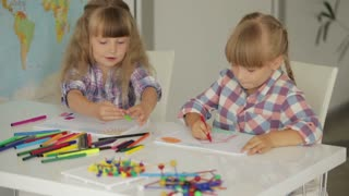 Two cute little girls sitting at table drawing with colored pencils and smiling