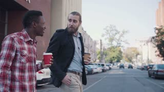 Two different people: caucasian and afro american, having a conversation till crossing street with cups of coffee in arms. Urban background
