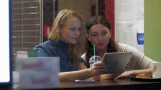 Two female friends are sitting in cafe in rainy day and watching photos in tablet PC. Shot is made through the cafe show window.