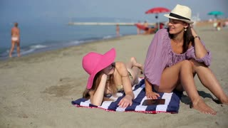Two female friends sitting on the beach and talking