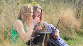 Two female friends sitting on the grass and talking online using laptop.
