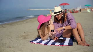 Two female friends with cellphone on the beach