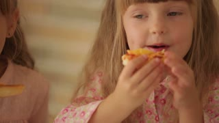 Two funny little girls eating pizza and smiling at camera