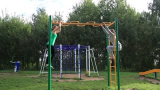 Two girls on sports ground making leg-split in the air hanging on sport equipment.
